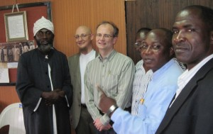 "Tjip Walker '79 (center) meets with Pastor James Wuye (right in blue shirt) and Imam Mohammed Ishafa (far left), co-founders of the Interfaith Mediation Center, Kaduna, Nigeria, a leading peacebuilding organization in Northern Nigeria and a recipient of USAID/OTI grants. ""Incidentally the Pastor and Imam have emerged as two of Nigeria's most influential peacebuilders,"" writes Walker, ""joining forces in 2000 after sectarian riots ripped through Kaduna."""