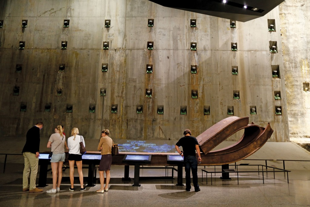 Visitors write messages on interactive tables in front of a steel column from the South Tower, folded over onto itself during the tower's collapse on 9/11. Photo: Jin Lee/911 Memorial.