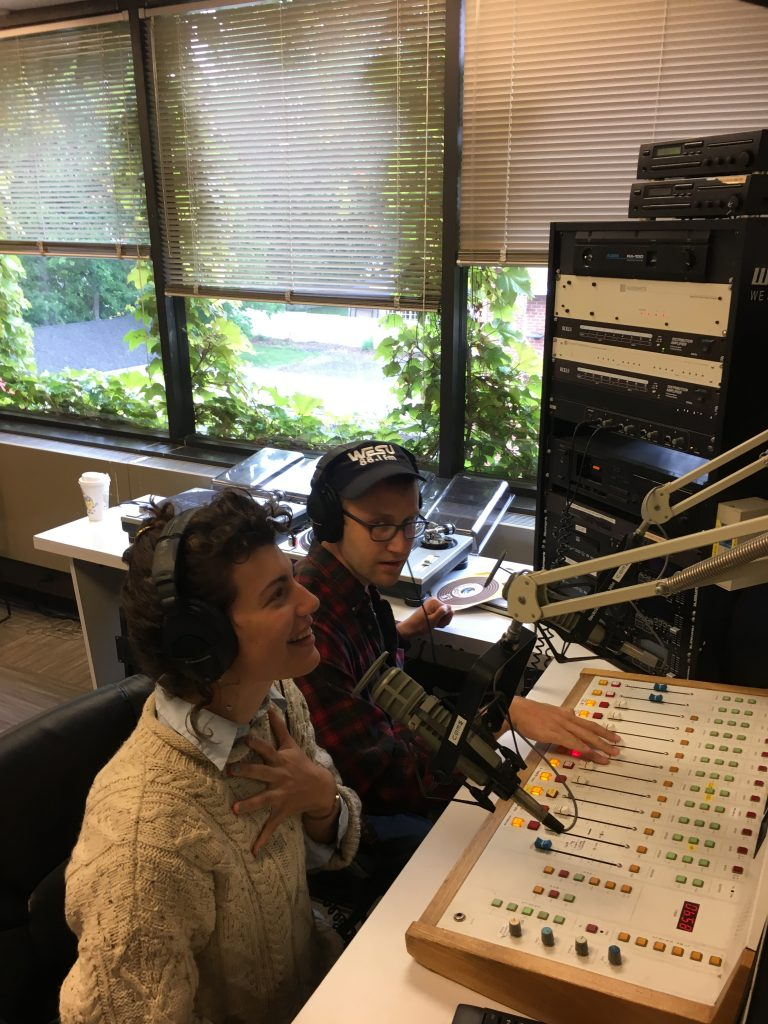 Avery Trufelman and Mickey Capper sit in the WESU studio and the sound board